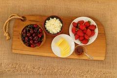 Plan rapproché de petit déjeuner sain : fromage blanc, fraises, cerise et fromage coupé en tranches sur le conseil en bois Rétro  photos stock