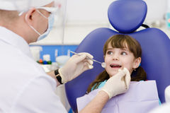 Plan rapproché de petite fille ouvrant le sien bouche au loin pendant l'inspection photographie stock