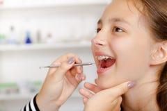 Plan rapproché de petite fille ouvrant le sien bouche au loin pendant le traitement de h Image stock