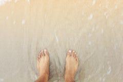 plan rapproché de pieds d'homme se tenant sur la plage ; émotion de concept de tristesse photos stock
