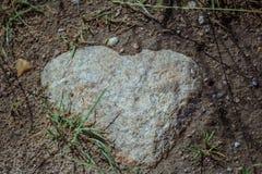 Plan rapproché de pierre en forme de coeur naturelle de granit dans le sol de champ Image stock