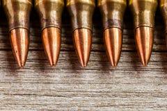 Plan rapproché de pleines balles de veste en métal de fusil dans une rangée sur le fond en bois avec l'espace de copie Images stock