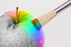 Plan rapproché de pomme d'arc-en-ciel avec des baisses de l'eau étant peintes sur un blanc Photos stock