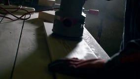 Plan rapproché de poncer un conseil en bois Les mains du forgeron rectifie lisse le conseil en bois pour rendre la surface lisse banque de vidéos