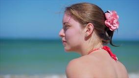 Plan rapproché de portrait d'une belle femme européenne sur la plage, examinant la distance la mer, détendant la mer banque de vidéos