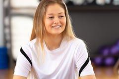Plan rapproché de portrait de sourire d'une femme de repos au centre de fitness Photos stock
