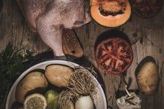 Plan rapproché de poulet entier avec des légumes sur la table Image stock