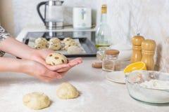 Plan rapproché de préparer et de former les petits pains croisés de Pâques avec des raisins secs hors de pâte Image libre de droits