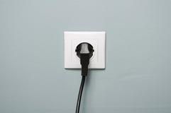 Plan rapproché de prise électrique avec le câble noir branché Images stock