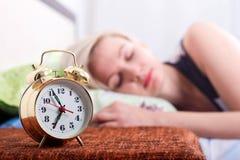 Plan rapproché de réveil et de jeune femme blonde de sommeil dans la chambre à coucher lumineuse à la maison, matin photographie stock