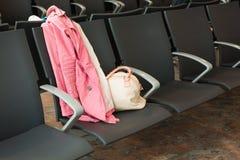 Plan rapproché de sac à main et de manteau sur la chaise à l'aéroport Voyage, vacances, concept d'affaires Image stock