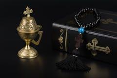 Plan rapproché de Sainte Bible, perles de chapelet avec la croix et encensoir sur le fond noir Concept et foi de religion photographie stock libre de droits