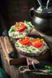 Plan rapproché de sandwich avec du fromage de fromage, ciboulette et tomates-cerises Image stock