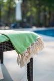 Plan rapproché de serviette turque verte et blanche sur le canapé de rotin avec la piscine bleue comme fond Photographie stock libre de droits