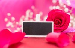 Plan rapproché de signe vide de tableau noir avec la rose et les pétales de rouge, sur le fond rose Images stock