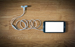 Plan rapproché de smartphone noir avec l'écran blanc avec des écouteurs dessus Photos libres de droits