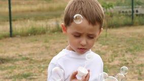 Plan rapproché de soufflement de bulles de savon d'enfant heureux Bulles volant dans le vent dans le mouvement lent banque de vidéos