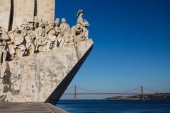 Plan rapproché de statue de navigateurs dans le Tage avec la passerelle de séjour de câble à l'arrière-plan à Lisbonne, Portugal Photographie stock libre de droits
