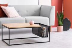 Plan rapproché de table basse moderne en bois et en métal à côté de divan gris élégant dans le salon à la mode photo stock