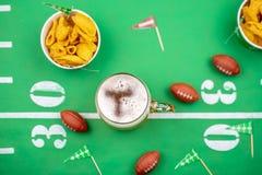 Plan rapproché de tasse de décorations de bière et du football sur la table pour le gam images libres de droits