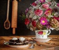Plan rapproché de tasse de thé avec le bouquet de gâteau et de fleurs sur la fin en bois de table vers le haut de la photo Images stock