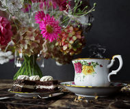 Plan rapproché de tasse de thé avec le bouquet de gâteau et de fleurs sur la fin en bois de table vers le haut de la photo Image libre de droits