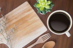 Plan rapproché de tasse de plat de café noir et en bois sur une table en bois photos stock