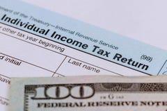 Plan rapproché de temps d'impôts d'U S déclaration d'impôt 1040 avec 100 factures Images libres de droits