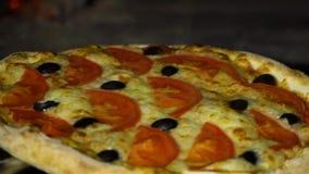 Plan rapproché de tenir la pizza sur la pelle à fer à l'intérieur du four traditionnel dans le mouvement lent banque de vidéos