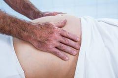 Plan rapproché de thérapeute massant le ventre de la femme enceinte images stock