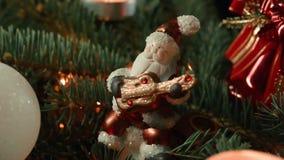 Plan rapproché de Toy Santa sur l'arbre de Noël avec les boules et la bougie de Noël banque de vidéos