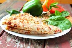 Plan rapproché de tranche de pizza avec la tomate et l'herbe de poivron vert Photographie stock