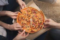 Plan rapproché de trois amie prenant des tranches de pizza Photo libre de droits