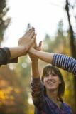 Plan rapproché de trois femmes joignant des mains haut dans le ciel Photographie stock