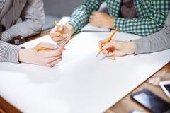Plan rapproché de trois paires de mains travaillant sur un nouveau projet Le dessin du plan photographie stock