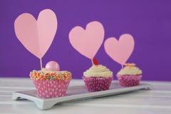 Plan rapproché de trois petits gâteaux délicieux avec des cartes de forme de coeur dans le plateau Images stock
