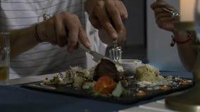 Plan rapproché de viande de coupe de l'homme du plat et de l'offrir à son amie pour le goûter dans un restaurant banque de vidéos