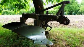 Plan rapproché de vieille charrue en acier brillante dans l'arrangement rural photo stock