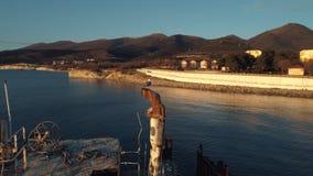 Plan rapproché de vieux et détruit tronc de bateau et mouette se reposant sur un tuyau rouillé contre le ciel de coucher du solei banque de vidéos