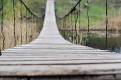 Plan rapproché de vieux long pont de corde en bois à travers une rivière Image stock