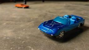 Plan rapproché de voiture bleue de jouet pour des enfants sur le fond divers avec la voiture orange de jouet sur le fond photo libre de droits