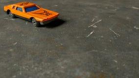 Plan rapproché de voiture orange de jouet pour des enfants sur le fond divers photographie stock