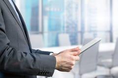 Plan rapproché de vue de côté d'un homme d'affaires qui passe en revue sur son comprimé Photo libre de droits