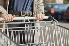 Plan rapproché de vue de face avec un centre sélectif d'une adolescente déplaçant un caddie en dehors d'un supermarché images libres de droits