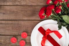 Plan rapproché de vue supérieure de la portion romantique de dîner avec les roses rouges d'un bouquet et du présent au-dessus du  Photos libres de droits