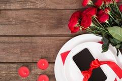 Plan rapproché de vue supérieure de la portion romantique de dîner avec les roses rouges d'un bouquet et du présent au-dessus du  Photo stock