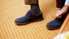 Plan rapproché, dentelles de lien des mains des hommes l'homme met sur ses chaussures bleues élégantes de suède, sur le fond de t banque de vidéos