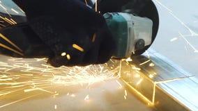 Plan rapproché des étincelles du profil circulaire en métal de coupe de machine de meulage dans l'atelier banque de vidéos