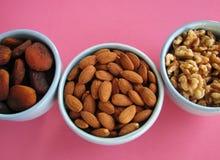 Plan rapproché des abricots secs, des amandes et des moitiés de noix dans des cuvettes bleues sur le fond rose Images stock