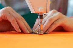 Plan rapproché des affaires du ` s de tailleur - mains femelles derrière sa couture Photographie stock